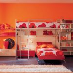 orange painted wall wooden bookshelves red painted bedframe red painted wardrobe door orang floral bedsheet dark gray ceramic tiled comfortable creame rug cute kids' room