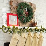 pine-leaves wreath decoration for mantel family picture in red frame unique shelving unit with two white dear miniature a white candle stand