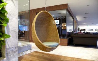 rattan hanging chair unit with white pillow  hardwood floors