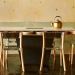 raw concrete wall raw concrete floor wooden dining chair with steel accent wooden dining table golden small teapot dining unit of The Line Hotel in Koreatown Los Angeles