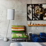 raw concrete wall unique standing lamp colorful chair unique blue coffee table wooden shelf beautiful painting white window frame raw interior design of The Line Hotel in Koreatown Los Angeles