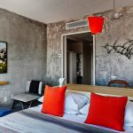 raw concrete wall white painted ceiling simple red pendant lamp red cushions wooden headboard and table unique blue coffee table wooden shelf raw interior deign of The Line Hotel in Koreatown Los Angeles