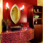 red and yellow wall yellow ceiling stone tiled flooring purple mosaic tiled vanity wood bathroom cabinet glass vase unique purple metallic sink red towel oval mirror with metal frame white sconces