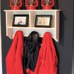 red lanterns black. red, and white wall white wall mounted shelf two black framed photos red and black hanging jackets.