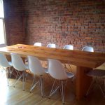 simple white office chairs long wood desk top red brick walls for office glowy wood flooring