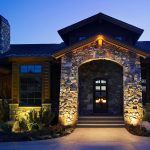 stoned exterior wall wooden front door frame stoned walkways wooden exterior wall beautiful lighting for front entry beautiful front entry well groomed front yard