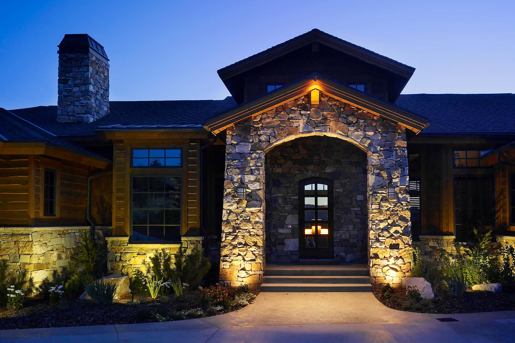 Creating an enchanting front entry with architectural details stoned exterior wall wooden front door frame stoned walkways wooden exterior wall beautiful lighting for front aloadofball Image collections