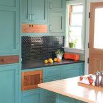 turquois cabinets wood door with black knob cute turquois island with wood countertop gren wall white framed window black tiled backsplash black counter green and white pots