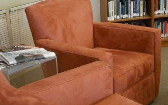 velvet-coat reading chair large book shelves glass-top table basket weave carpet