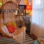 webbing rattan hanging chair colorful decorative pillows colorful rugs unique orange table lamp white lace curtain