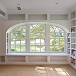 white bookshelves  and bench under curve-window style side-bookcase natural brown basket weave carpet