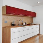 white ceiling white wall laminate wood flooring white cabinet with iron handles wood countertop wood backsplash red cupboard with iron handle silver undermount sink arc iron faucet