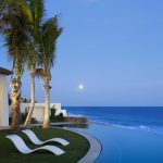 white contemporary curved seats gorgeous infinity pool calming beach scenery grey stone pool border white patio white wall brown chairs grey concrete patio flooring