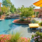 white pool with free shape yellow deck chair yellow patio umbrella beutiful flowers around the pool yellow chairs raw brick wall stone fireplace wood pergola white framed window