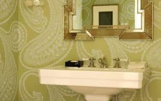 white standing sink patterned green wallpaper beautiful gold shell hanging sconce black tissue box black table elegant gold framed mirror black soap container white framed hanging artwork