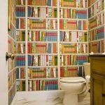 white toilet white ceiling fully stored bookshelves wallpaper white wall white with grey splash tiled flooring wood antique light brown vanity white door