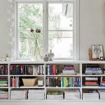 white under windows bookcase with huge glass glass vase and artificial flower ornaments  frameless human_s skets painting  pile of books  books arrangements white subway tiles floor