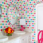 white vanity with white sink glass square vase pink table lamp with white cover round mirror with metal frame pink chair with white cushion white door colorful polka dot wallpaper and ceiling