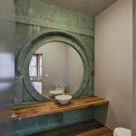 white wall white ceiling silver ceiling lamp green granite wall white bowl sink floating wood vanity white toilet big round mirror grey bathroom door