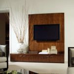 wood TV stand cabinetry with natural wood-line patterns white ornamental porcelain vase flat TV planted on the wood wall system