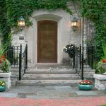 wooden door stoned exterior wall gray ceramic fornt entry door black painted metal fence beautiful wall mounted lamps stoned and bricked walkways beautiful front entry