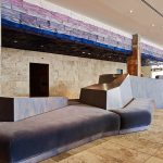 wooden floor concrete wall rustic column futuristic lobby chair white painted ceiling rustic meets modernity lobby hotel design The Line Hotel in Koreatown Los Angeles