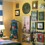 yellow wall white ceiling wood side table black table lamp with white cover black and white striped curtain black unique clock dark gree kimono with blue umbrella decoration colorful bed cover