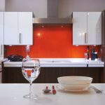 Acrylic Backsplash In Bright Orange Color White Acrylic Cabinets System  Acrylic White Countertop Acrylic Kitchen Island In White Tone A Set Of Dishware On Top Kitchen Island Modern Kitchen Tools