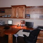 a home office with floating wood cabinet and shelves  an office desk with unique-shape panel divider in the center two laptop units a printer machine a fax machine a black movable office chair