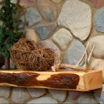 a piece of cedar mantel for fireplace with dry-roots ornament large river stones wall-system