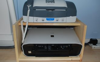 a printer machine and a fax machine are set on wood desk
