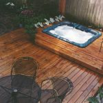 a rustic wood deck with hot tub and black-tone outdoor furniture