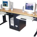 a standing computer desk for two persons with under sliding panels for keyboards and  under storage in the center two sets of computers with mini audio systems