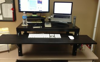 adjustable standing computer desk in black with big flat screen computer and laptop