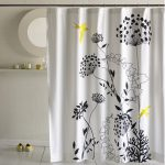 black big flower patterns in white shower curtain small white ceramic wall system a single floating shelf a round decorative mirror with white frame  a pair of yellow shoes white ceramic flooring