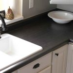 black-wood finish kitchen countertop with white decorative bowl a luxurious white sink with black-metal faucet