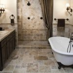 classic bathroom remodel with clawfoot white tub shower zone with dark shower curtain some classic wall-light fixtures bathroom vanity with oval semi-deep sink and faucet classic-frame decorative mirror