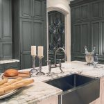 classic kitchen design with white marble countertop with deep black sink and stainless steel faucet two candle  stand fixtures two bottles of wine a wine glass some pieces of bread and a pile of flat plates