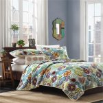 colorful flower-patterns bedding some small fired-clay flower pots with fresh and green plant ornaments classic-style mirror for bedroom brown carpet large glass windows with white frames