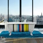 colorful strips- patterns free standing tub large black wood-framed glass windows bright blue fury carpet laminated-wood planks floor