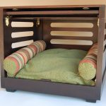 comfy dog crate with green bedding and pillows