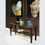 console table in rustic style with a pile of boxes and shield ornaments a table lamp  two large shield pictures