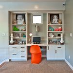 corner wall shelves  unit with desk in the center and under cabinetry two big-size picture frames in the shelves a laptop an orange plastic chair some decorative items