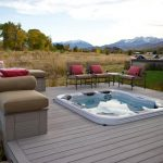 cozy home backyard wood deck with medium-size hot tub and two sets of patio furniture with red pillows