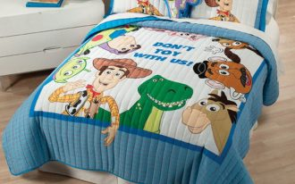 cute Toy-Story theme bedcover twin pillows with True Story figures  bedside table with drawers  a red table lamp softwood floor idea