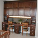 darkwood finish desk for two person with shelves and big cabinets and drawers two light brown wood chairs