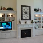 elegant white cabinets and shelves with full of decorative items and TV set  modern fireplace design in white with metal-wire decoration on its top