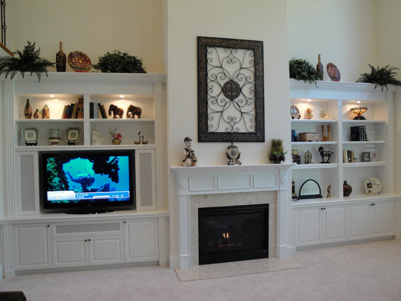 Elegant White Cabinets And Shelves With Full Of Decorative Items And TV Set  Modern Fireplace Design
