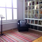 ethnic-patterns jaunty rug for wood floor a reading corner with a black leather reading chair and large bookshelf