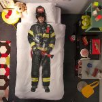 fireman costume as the focal point on a bed cover yellow round bedside table with table lamp a cute Teddy Bear colorful carpet cabinet system for boy's bedroom